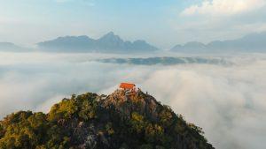 På toppen af et bjerg med flot udsigt udover et bjerglandskab.