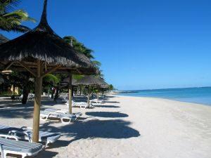Lækker badestrand på Mauritius med liggestole, parasoller og det azurblå hav i baggrunden